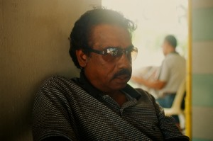An Indian man wearing sunglasses sitting a table outside.